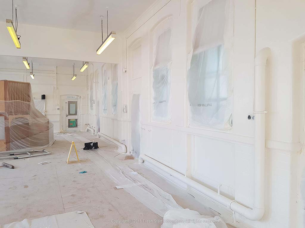 Sheeting and spray painting interior walls